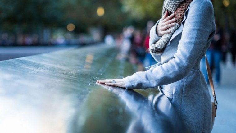 Frau legt ihre Hand auf einen Gedenktafel